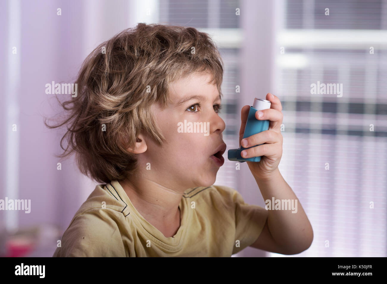 Boy using asthma inhaler to treat inflammatory disease, wheezing, coughing, chest tightness and shortness of breath. Allergy treating concept. - Stock Image