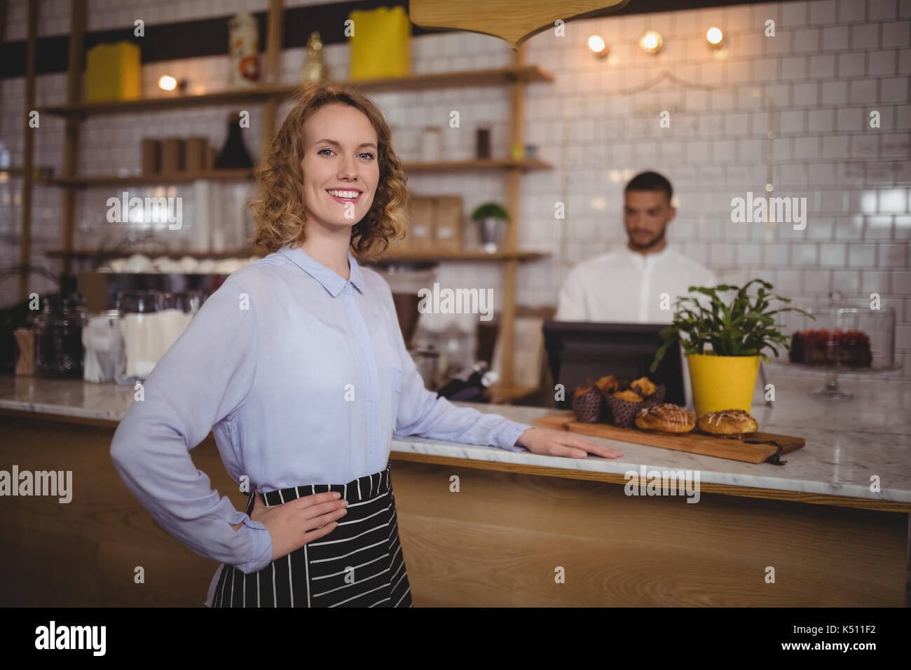 Portrait of smiling waitress standing with hand on hip by counter at coffee shop - Stock Image