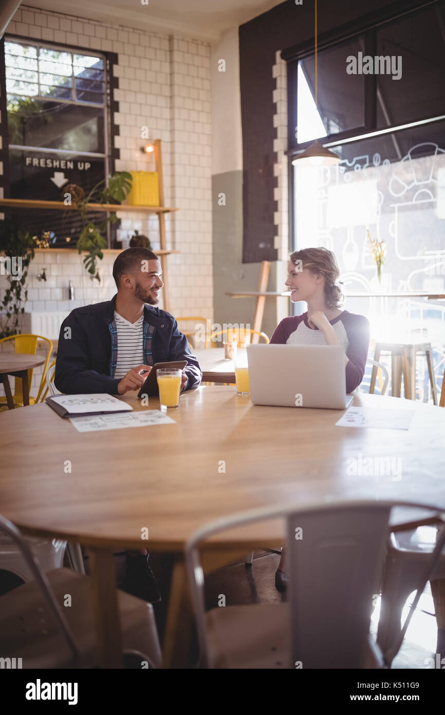 Smiling young friends talking while sitting with technologies at table in coffee shop - Stock Image