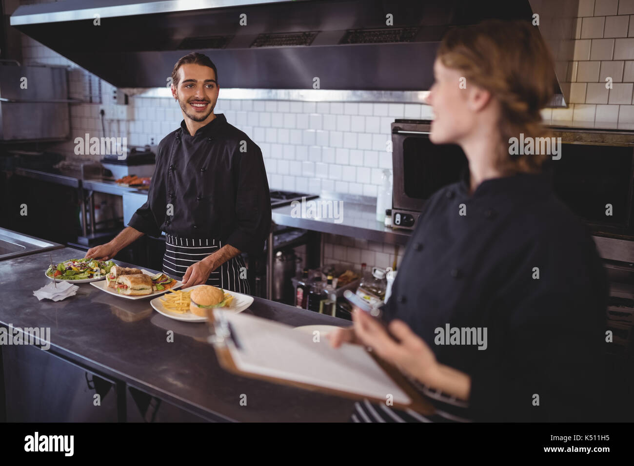 Young waiter preparing food while looking at waitress in coffee shop - Stock Image