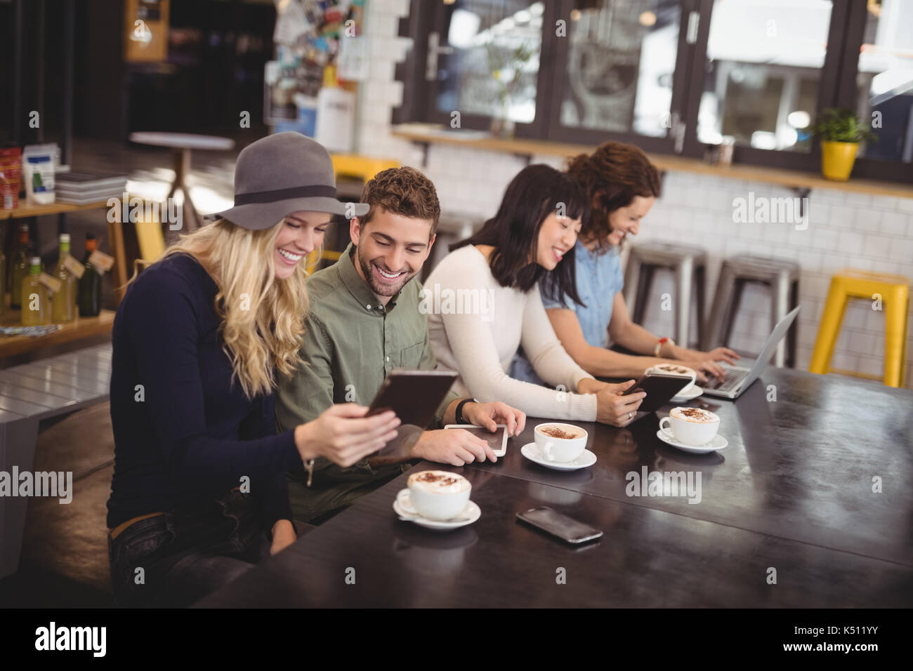 High angle view of happy friends using technologies while sitting at table in coffee shop - Stock Image