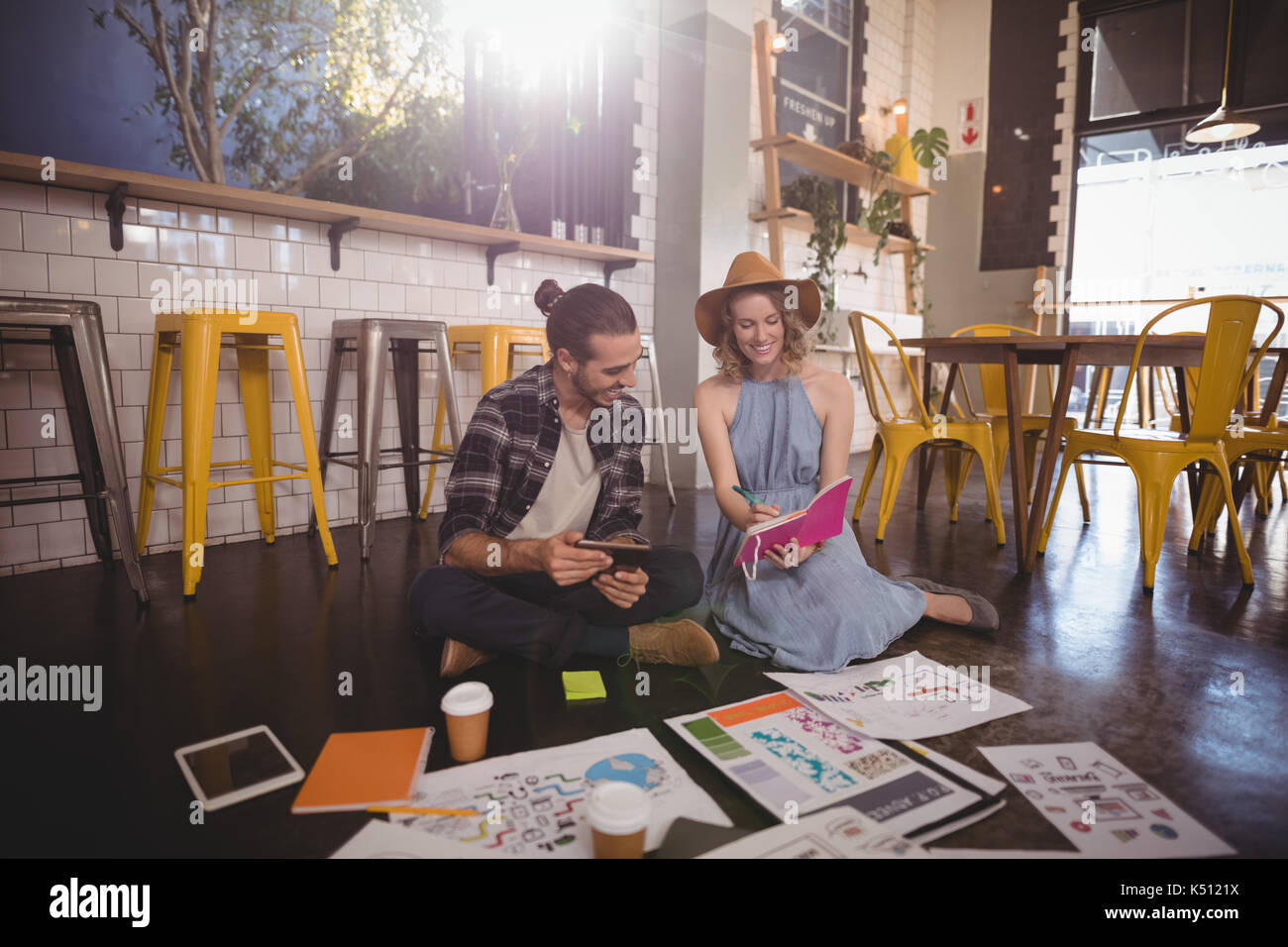 Young female professional showing dairy to male colleague sitting on floor at coffee shop - Stock Image