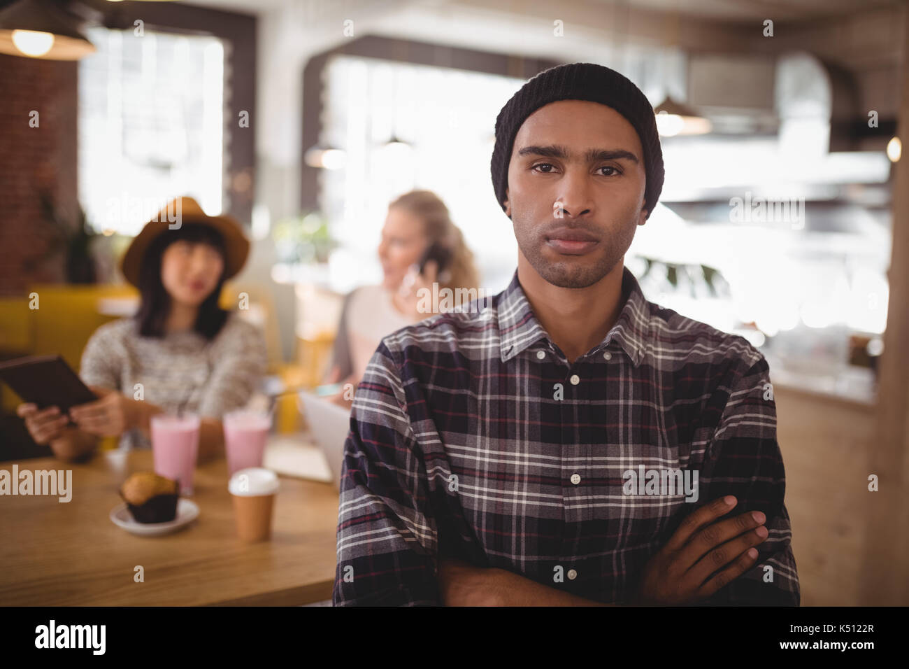 Portrait of confident young man with arms crossed standing against female friends at coffee shop - Stock Image