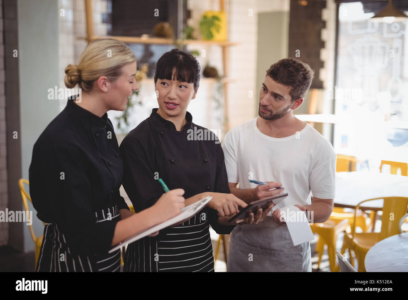 Young wait staff discussing over tablet computer while standing at coffee shop - Stock Image