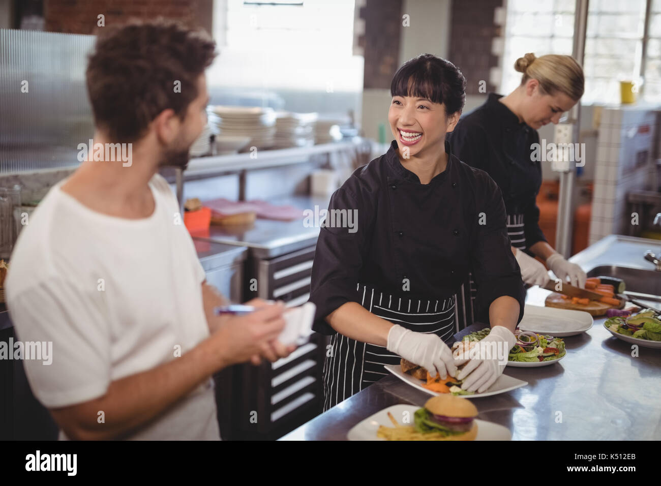 Cheerful waiter and female chef working in kitchen at cafe Stock Photo