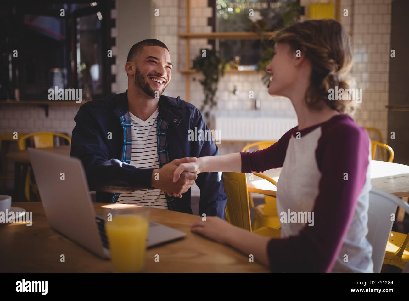 Smiling young friends shaking hands while sitting with laptop at coffee shop - Stock Image
