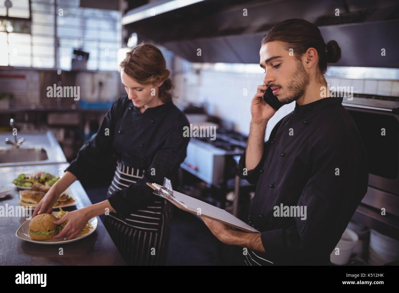 Young waiter talking on smartphone while waitress preparing food in commercial kitchen at coffee shop - Stock Image