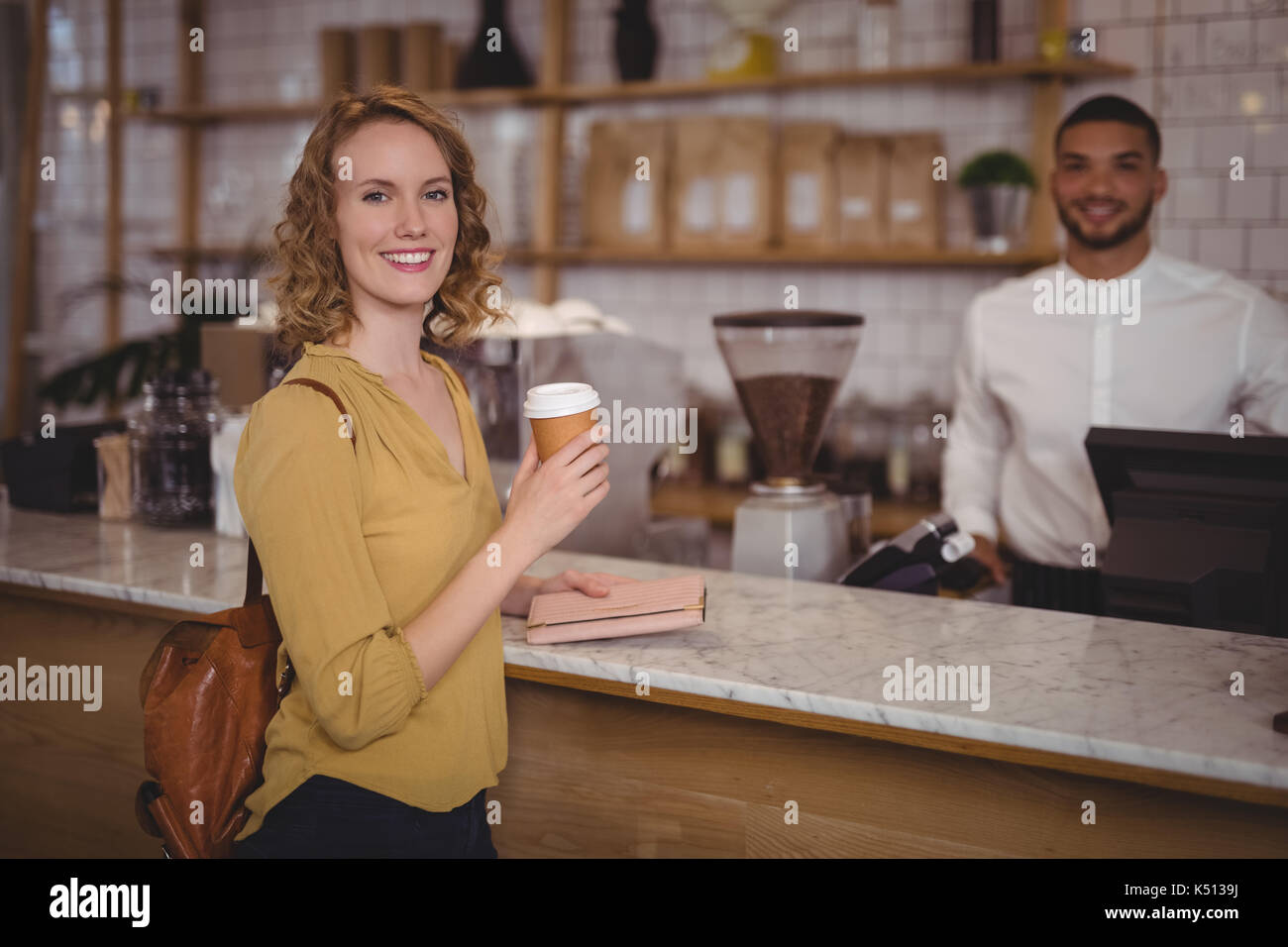 Portrait of smiling young female customer holding disposable coffee cup at counter against waiter in cafeteria - Stock Image