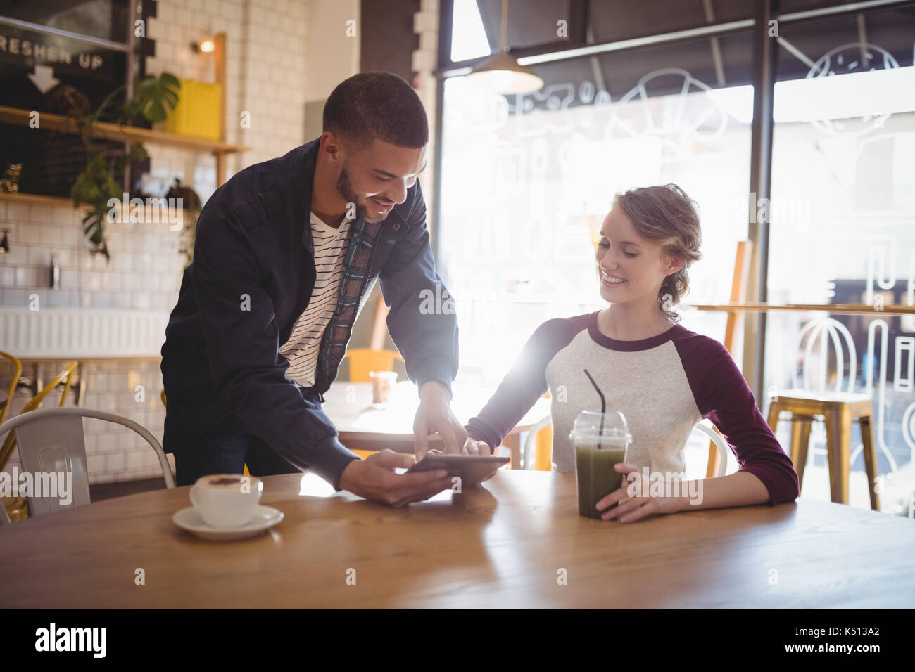 Young man showing digital tablet to woman at coffee shop Stock Photo