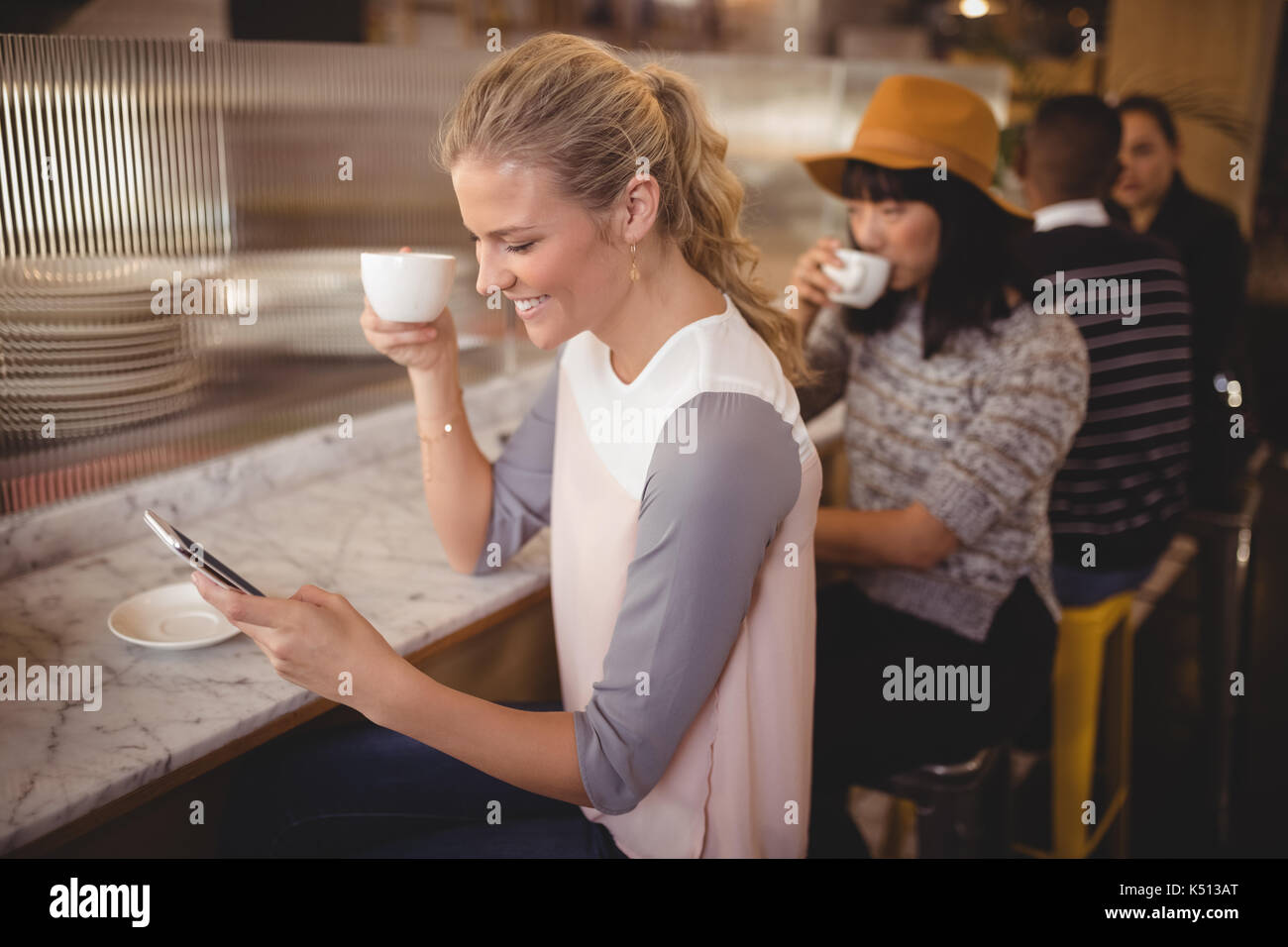 Young customers drinking coffee while sitting at cafe - Stock Image