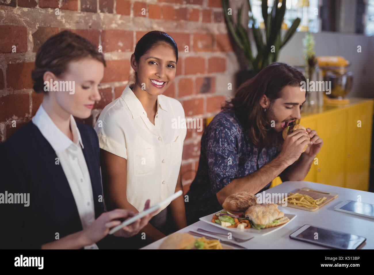 Portrait of smiling young woman sitting amidst friends at table with food in coffee shop - Stock Image
