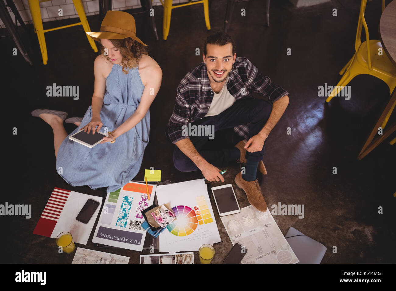 High angle portrait of smiling young male designer sitting by female colleague with sheets on floor at coffee shop - Stock Image
