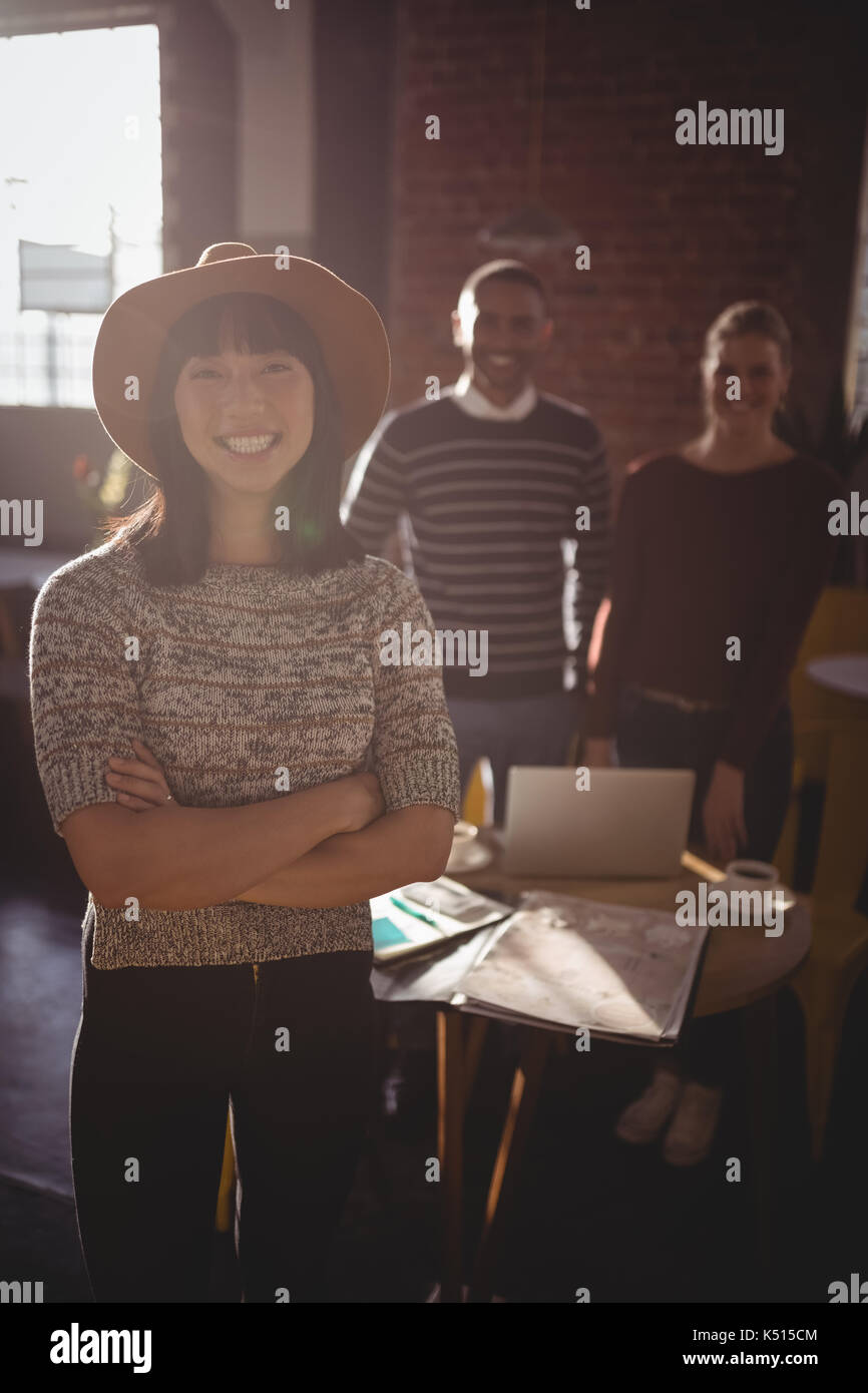 Portrait of smiling young woman wearing hat standing with arms crossed against colleagues at coffee shop - Stock Image