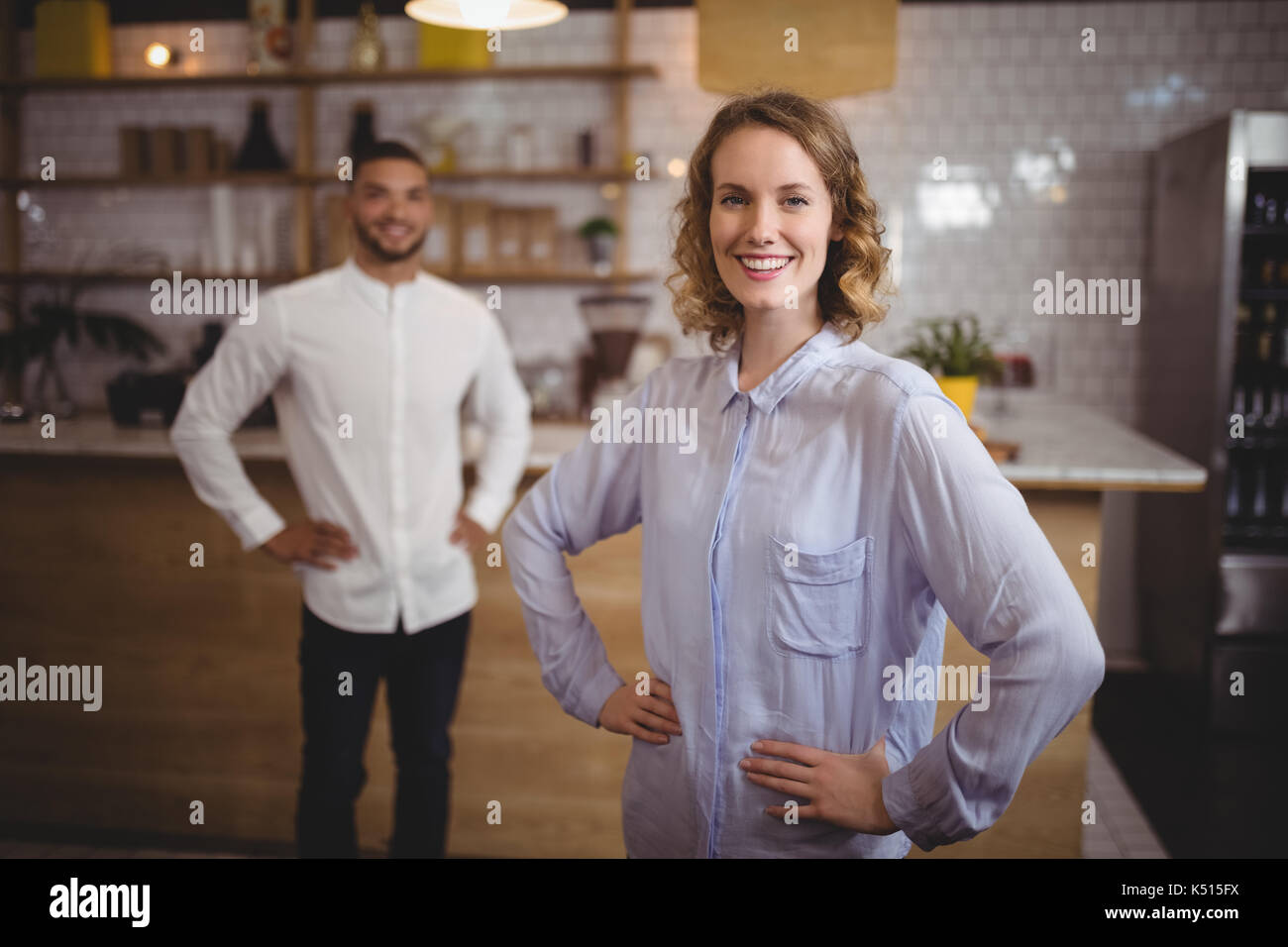 Portrait of smiling young woman with hand on hip against friend standing at coffee shop - Stock Image