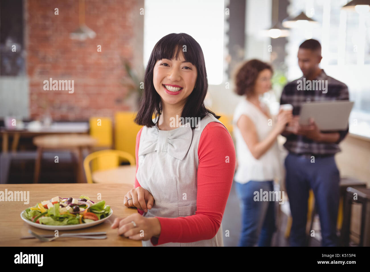 Portrait of smiling young woman sitting with fresh salad at table in coffee shop - Stock Image