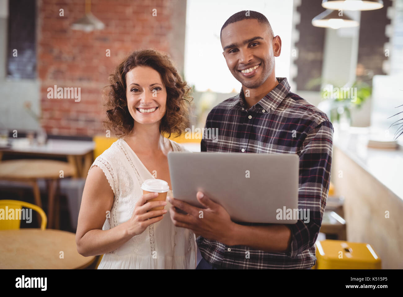 Portrait of smiling young friends standing with disposable coffee cup and laptop at cafeteria - Stock Image