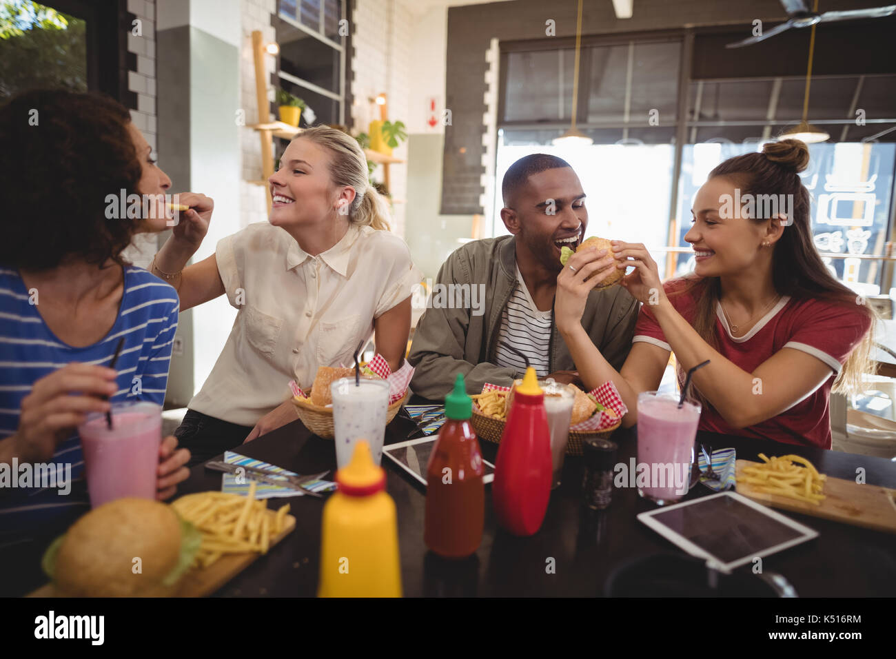 Young friends sharing food at table in coffee shop Stock Photo