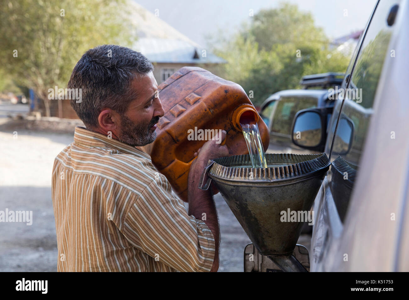 Tajik man with plastic container and funnel filling vehicle with fuel / gas along the Pamir Highway in Tajikistan - Stock Image