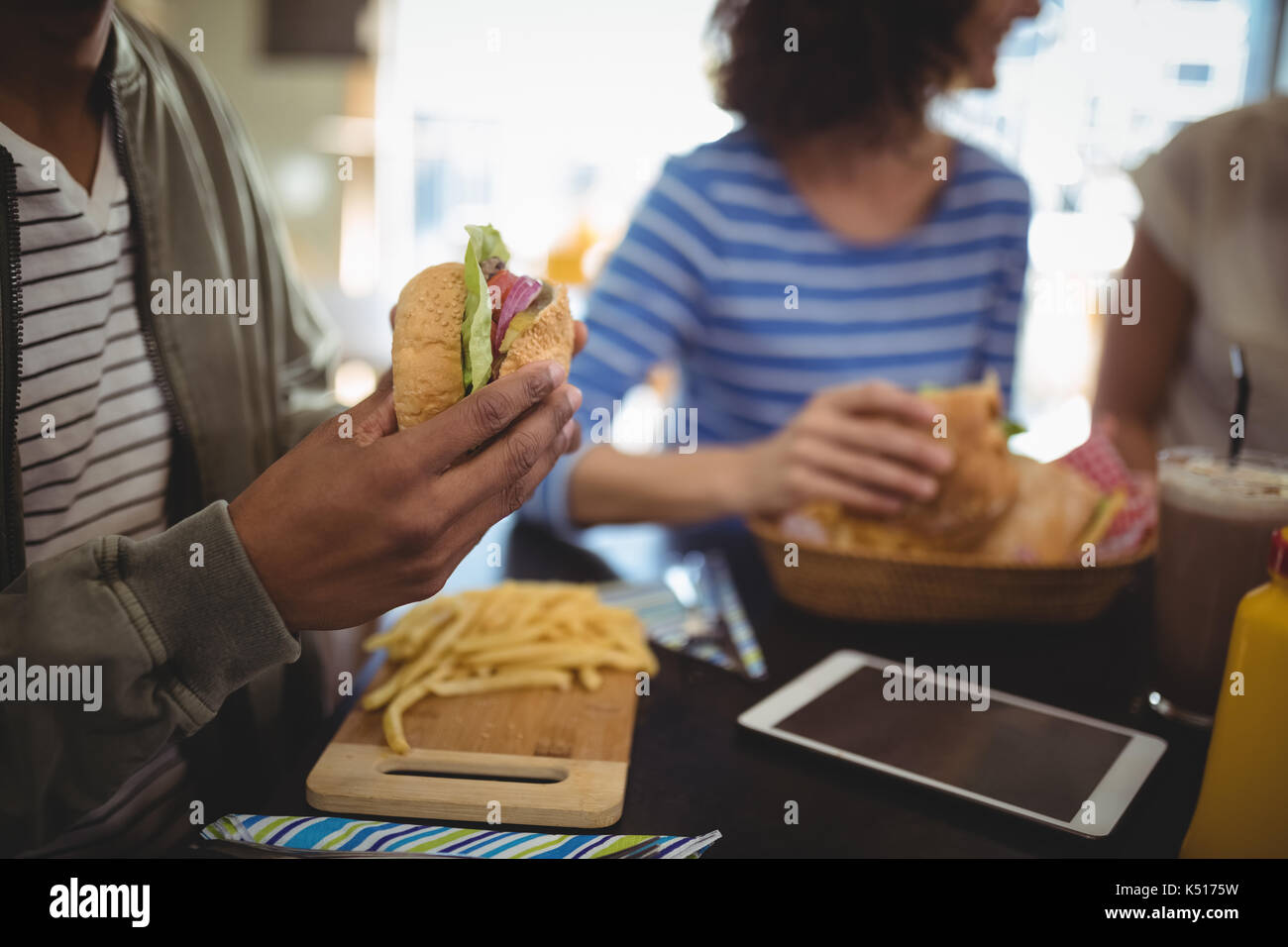 Midsection man holding fresh hamburger while sitting at table in cafe - Stock Image
