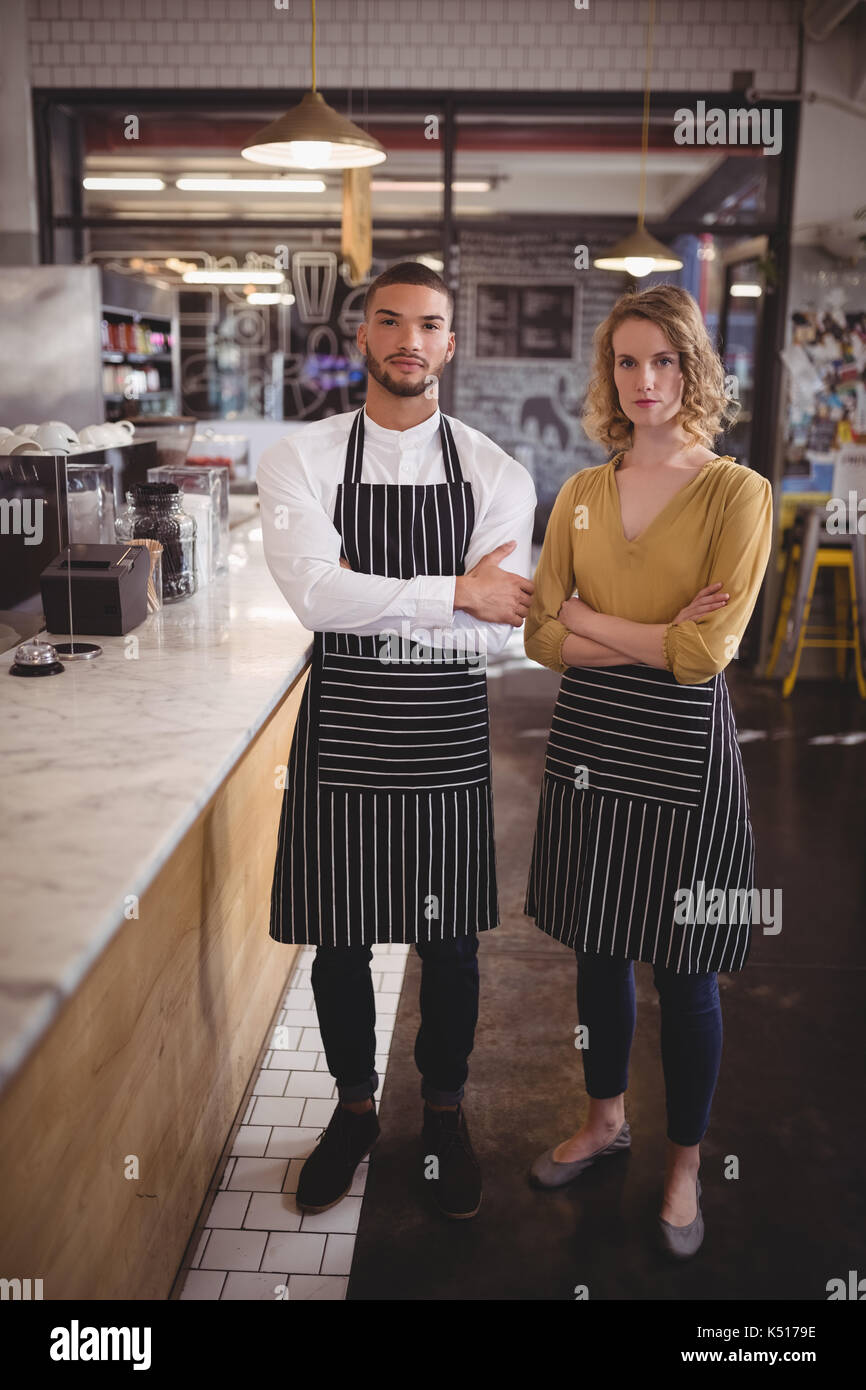 Portrait of confident young wait staff standing with arms crossed by counter in coffee shop - Stock Image
