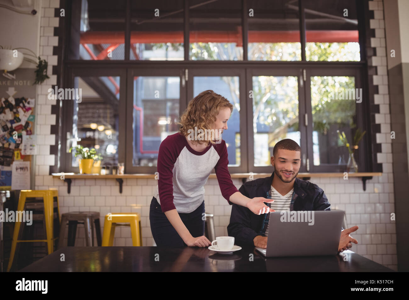 Young man and woman gesturing at laptop in coffee shop - Stock Image