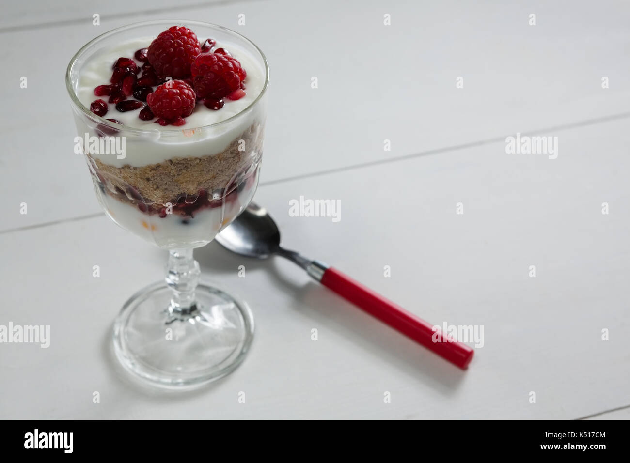 Cup of yogurt with raspberry and pomegranate on white background - Stock Image