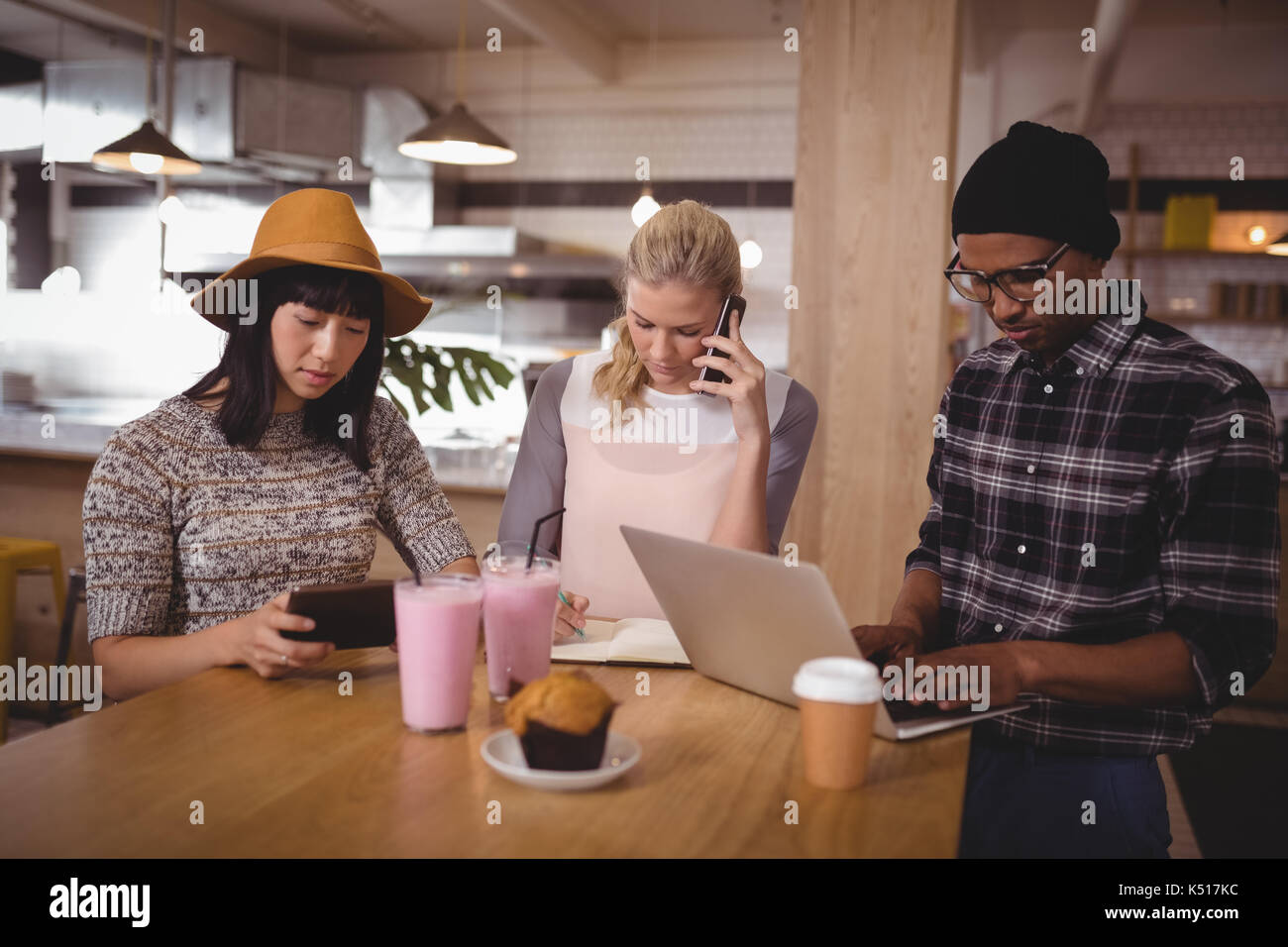 Young friends sitting at table while using technologies in coffee shop - Stock Image