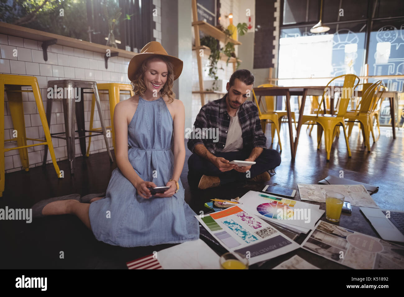 Young creative professionals using technologies while sitting with sheets on floor at coffee shop - Stock Image