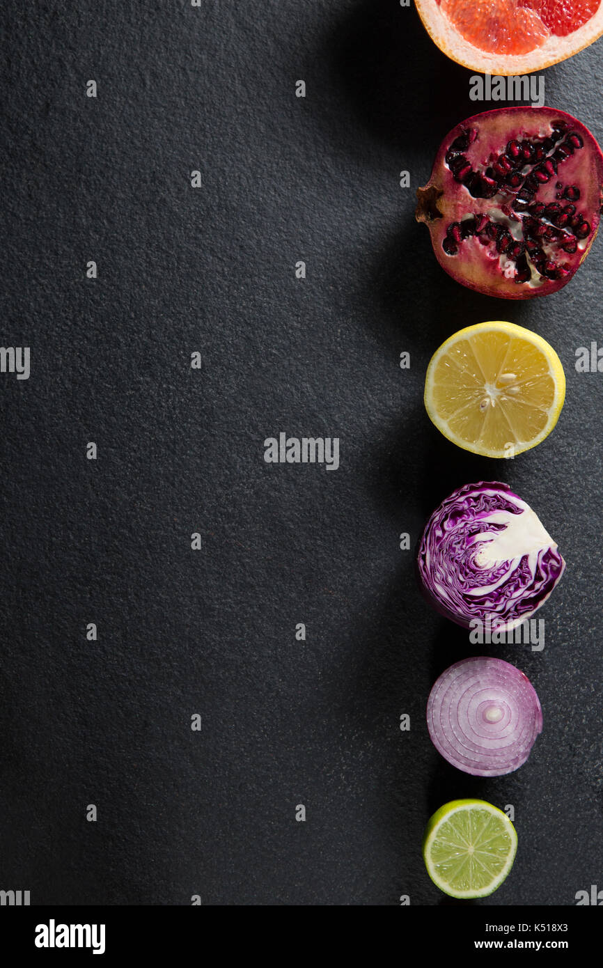 Overhead view of various fruits and vegetables arranged on gray slate Stock Photo