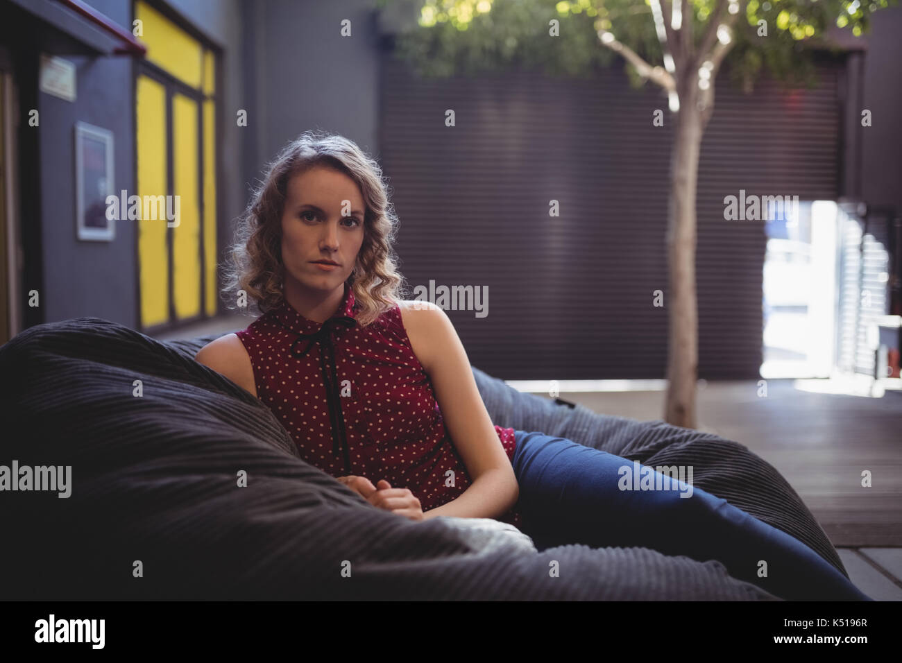 Portrait of beautiful young female customer sitting on bean bag against wall - Stock Image