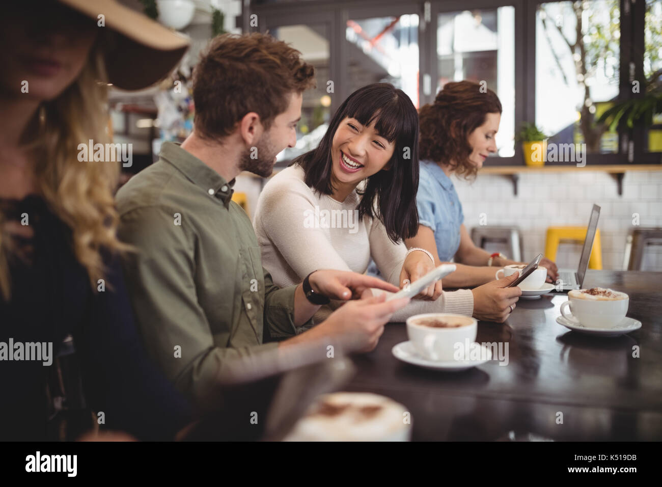 Smiling young friends talking while sitting at table in cafe Stock Photo
