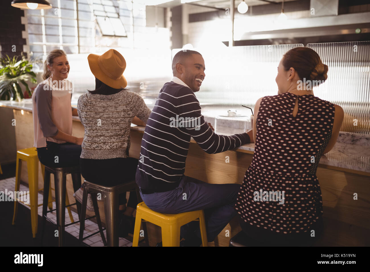 Cheerful young friends sitting table counter in coffee shop - Stock Image