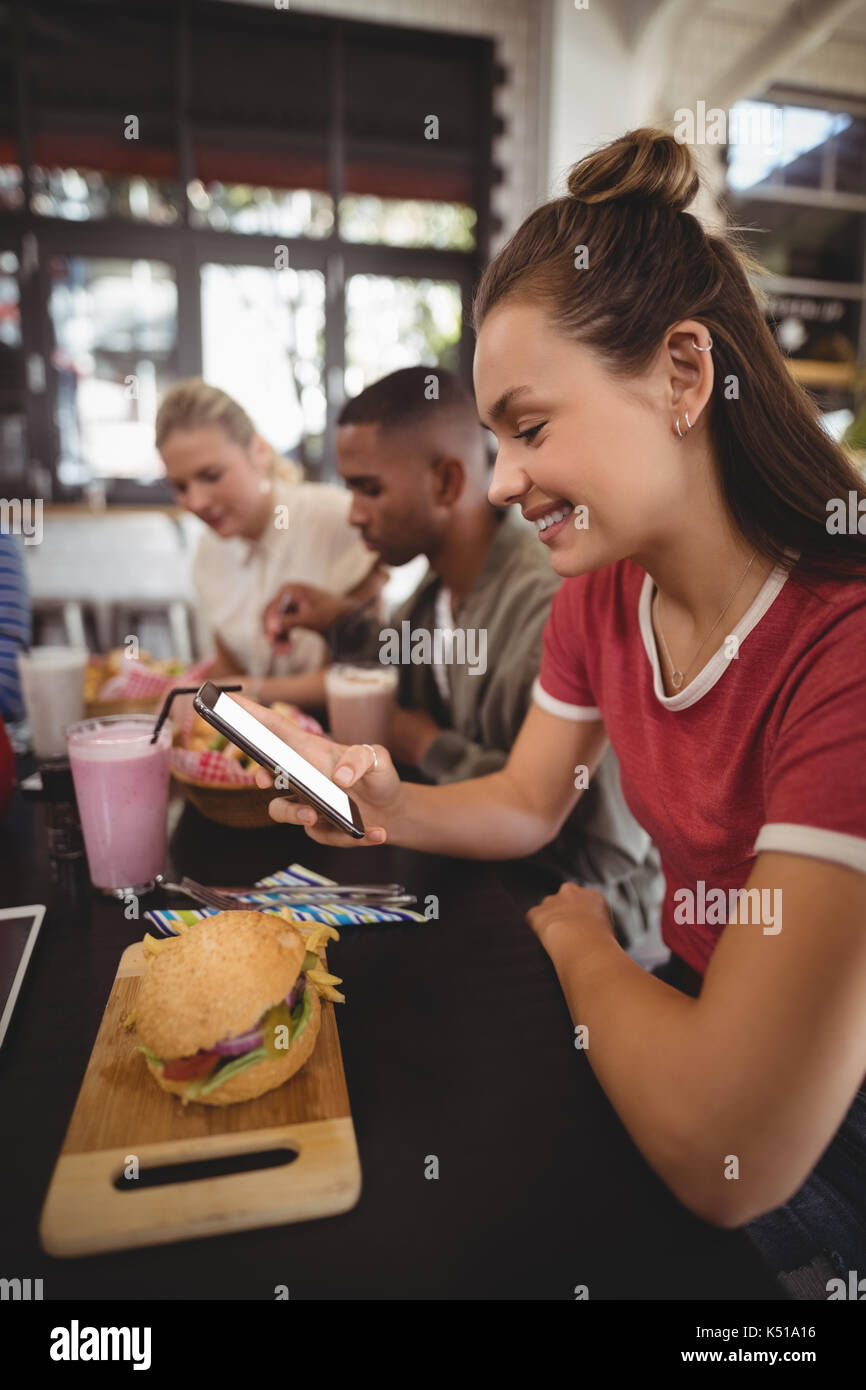 Side view of smiling young woman text messaging while sitting with burger at table in coffee shop - Stock Image