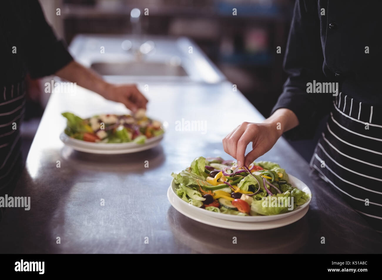 Midsection of waiter and waitress preparing fresh salad at counter in commercial kitchen - Stock Image
