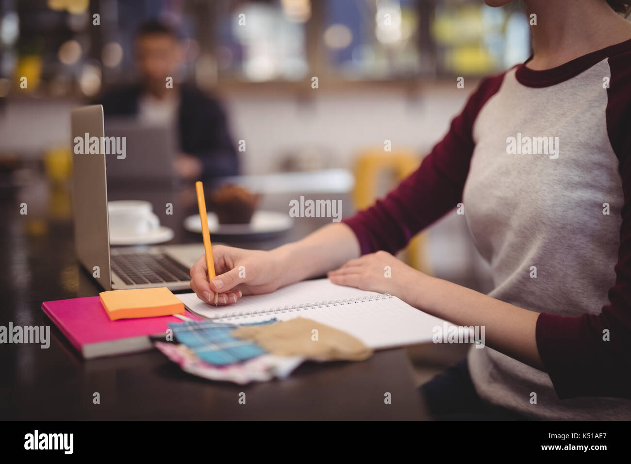 Midsection of design professional writing in dairy while sitting at table in coffee shop - Stock Image
