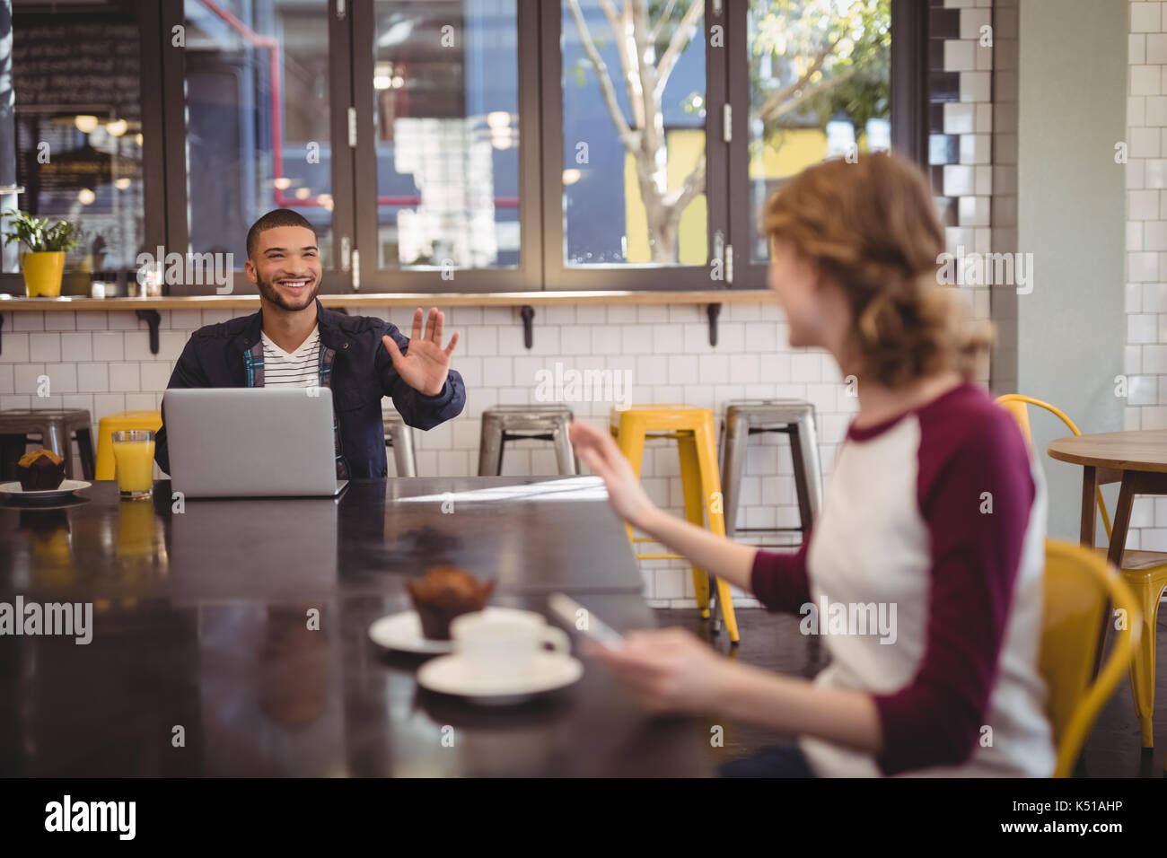 Young friends waving while sitting at table in coffee shop - Stock Image
