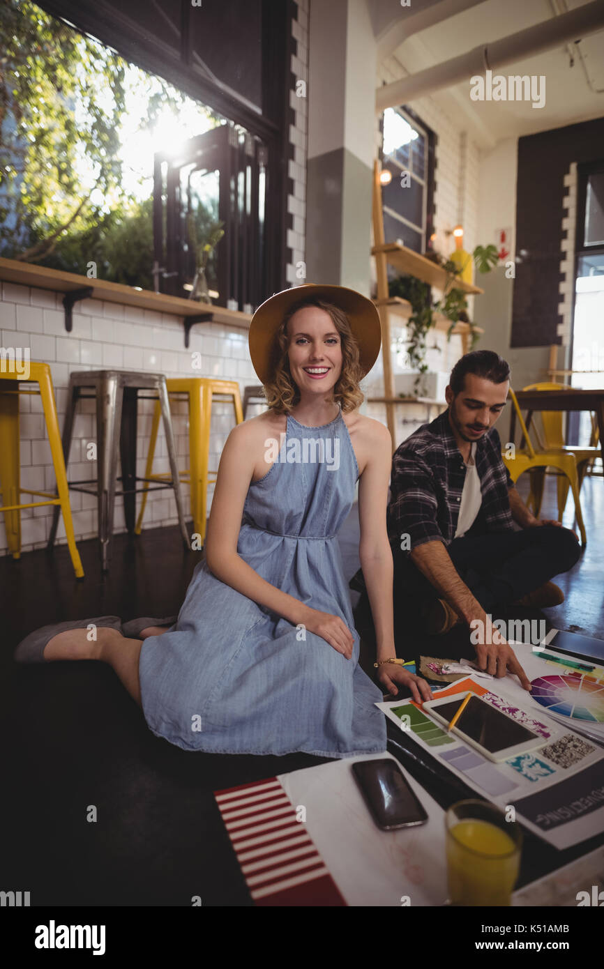 Portrait of smiling young female professional sitting with male colleague on floor at coffee shop - Stock Image