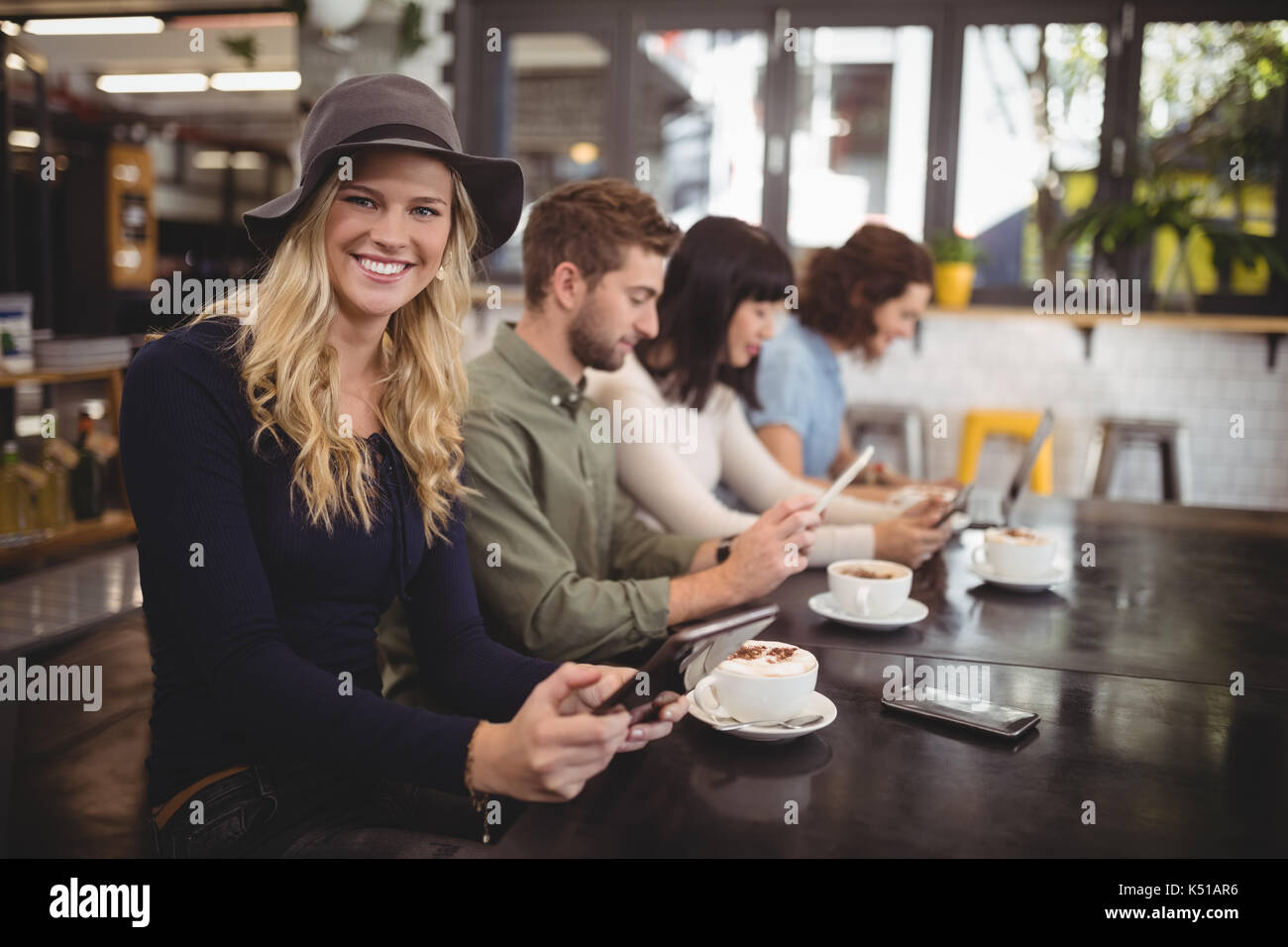 Portrait of smiling young woman sitting with friends at table in cafe Stock Photo