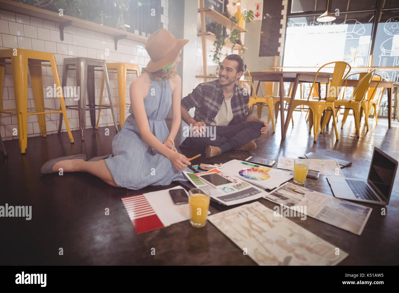 Smiling young professionals sitting with sheets and technologies on floor at coffee shop - Stock Image