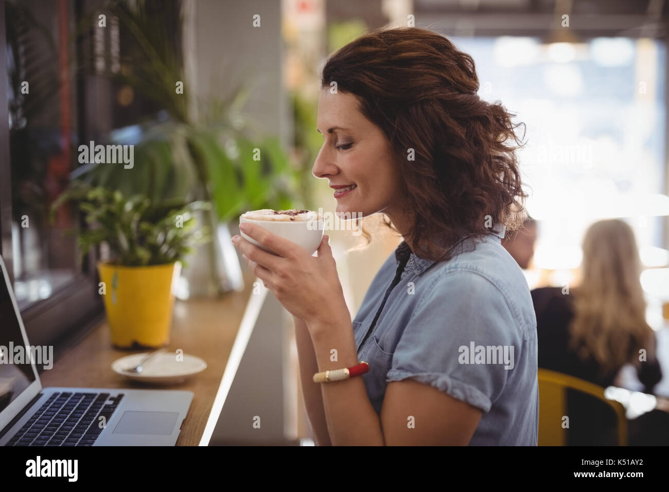 Side view of young woman smelling coffee while sitting at cafe - Stock Image