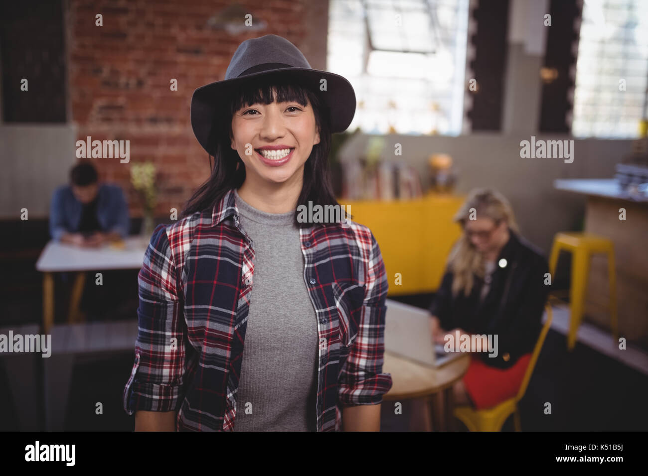 Portrait of smiling young woman wearing hat standing at coffee shop - Stock Image