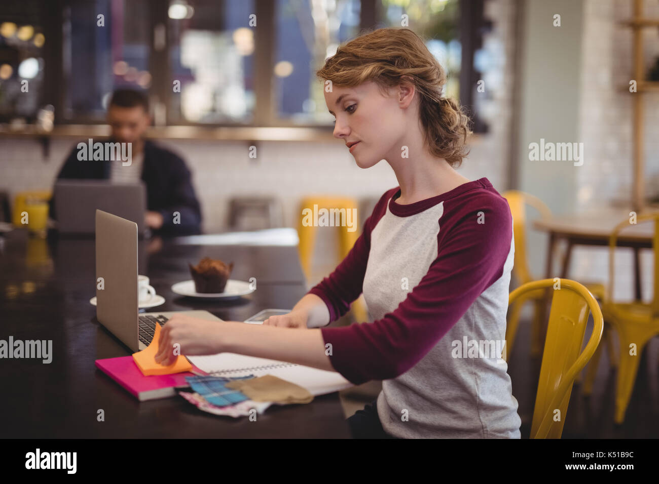 Confident young female designer sitting with notebooks and papers at table in coffee shop - Stock Image