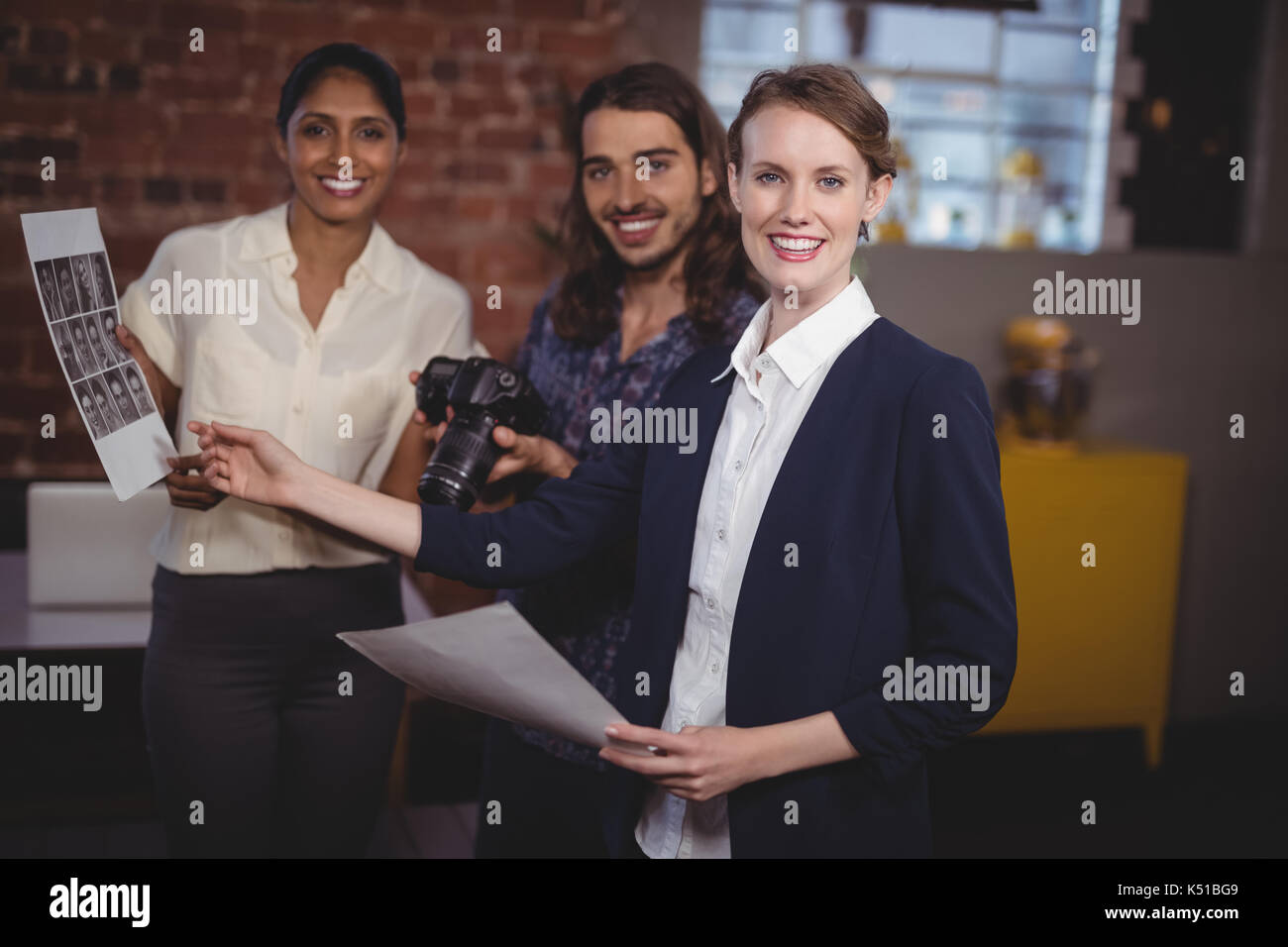 Portrait of smiling young creative team discussing collage at coffee shop - Stock Image