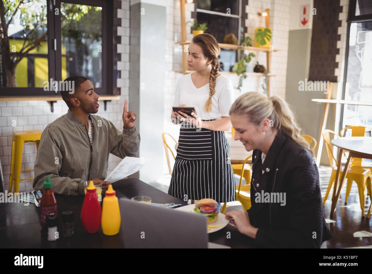 Young man ordering food to waitress while sitting with female friend at cafe Stock Photo