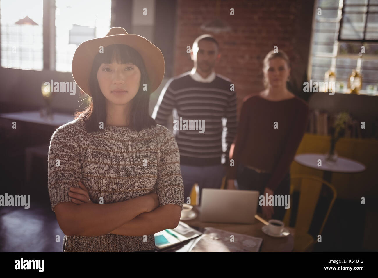 Portrait of woman wearing hat standing with arms crossed against colleagues at coffee shop - Stock Image