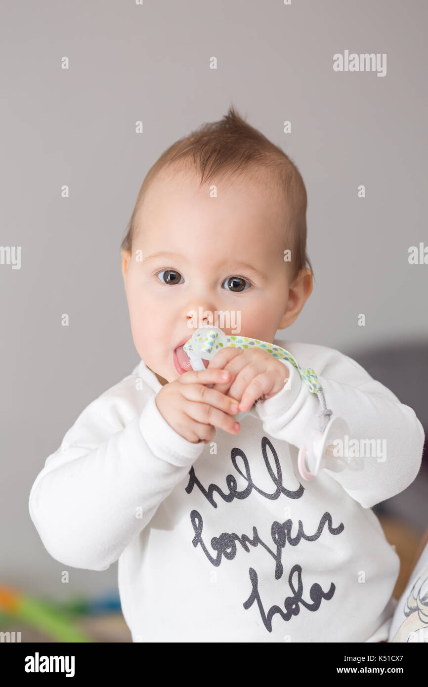 Eight months old baby girl bringing her pacifier to her mouth and sucking it - Stock Image