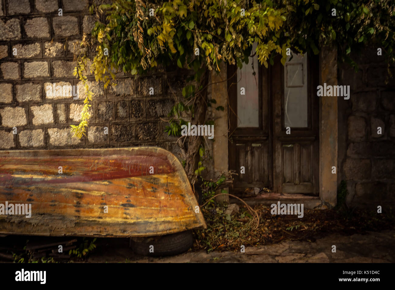 Vintage medieval building exterior on backyard with overturned old vintage sail boat in overcast day during raining autumn season in old European city - Stock Image
