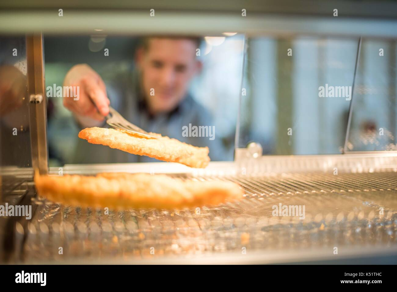A Uk fast food take away with worker reaching for battered fish and sausage - Stock Image