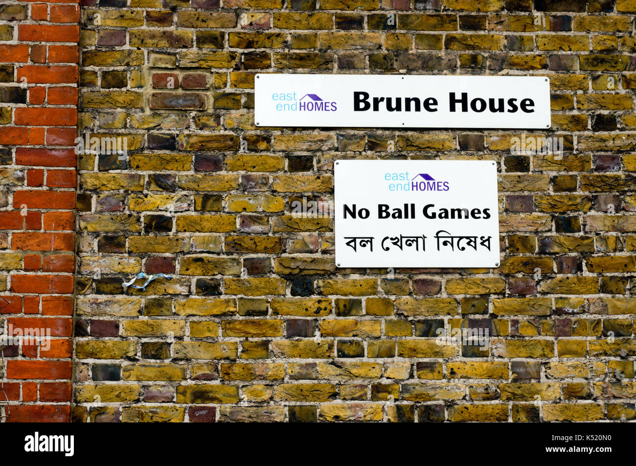 Bi-lingual sign in English and Bengali on side of housing association property in Whitechapel, East London. - Stock Image