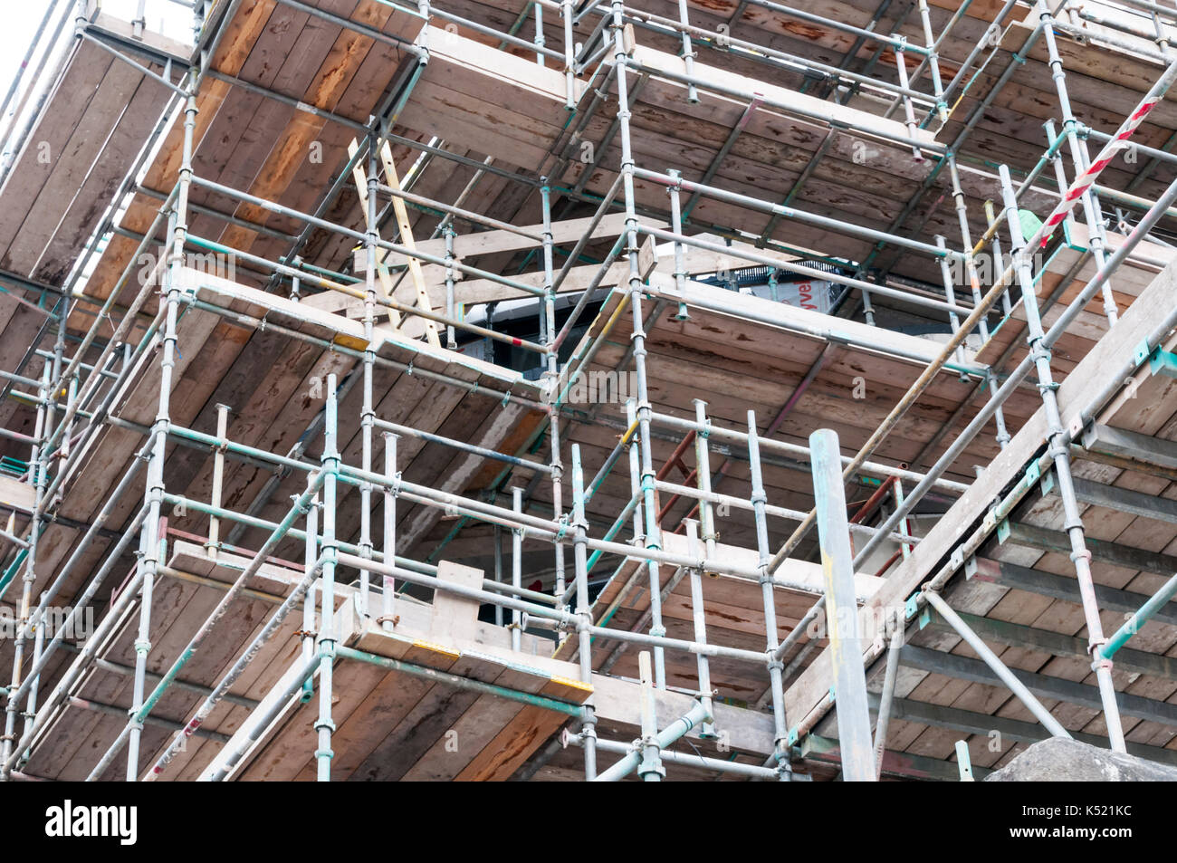 Comprehensive system of scaffolding and scaffold boards giving access to upper stories of building for maintenance work. - Stock Image